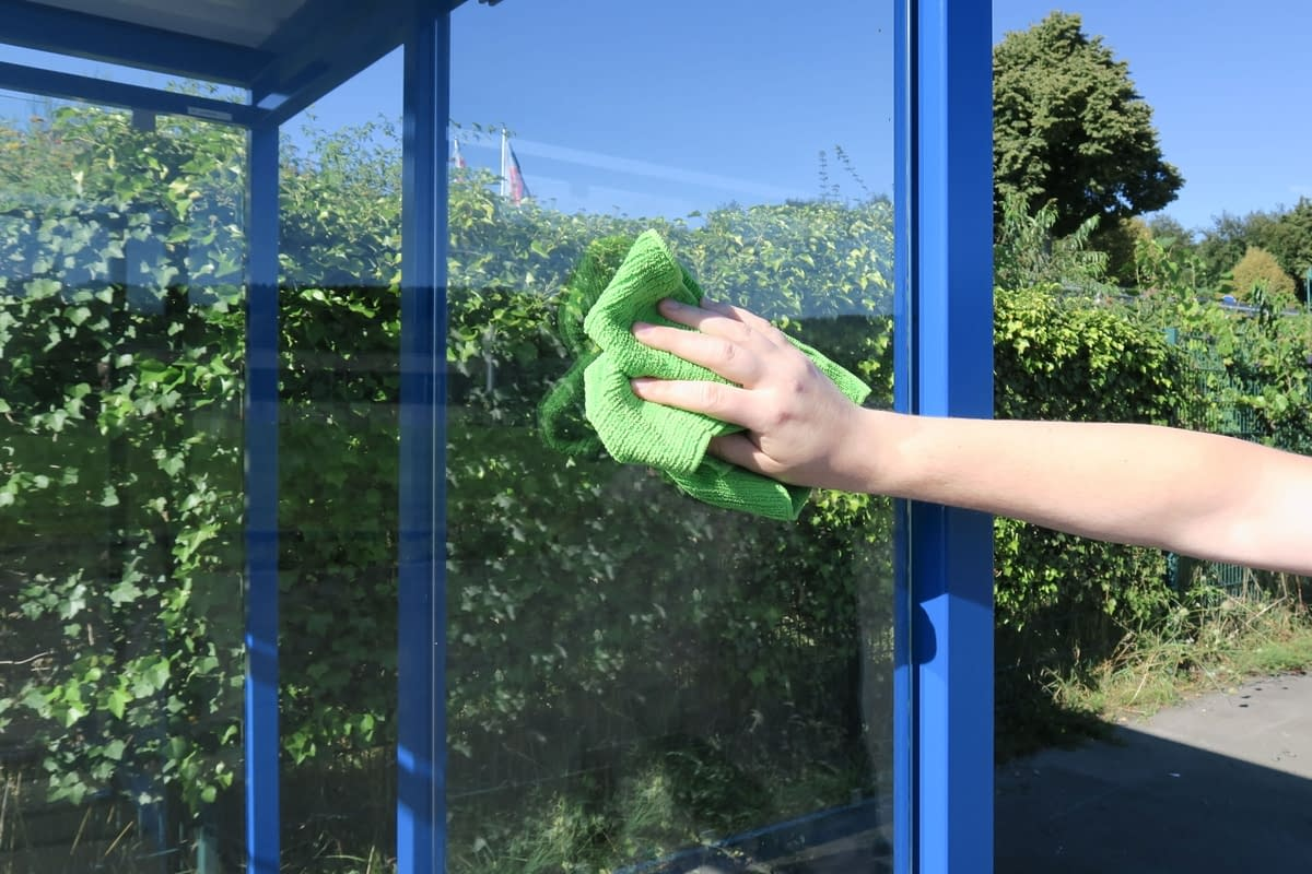 A man cleans a window pane with a rag