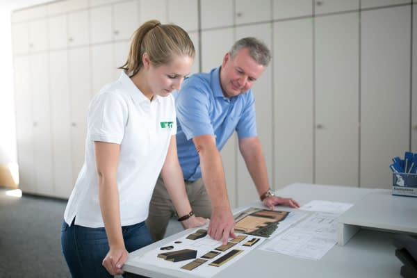 Trainee industrial clerk in front of plans for a room system