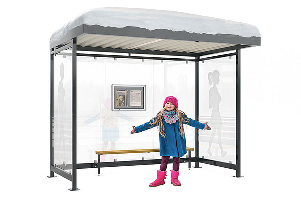 A young girl stands before a snowy bus stop shelter
