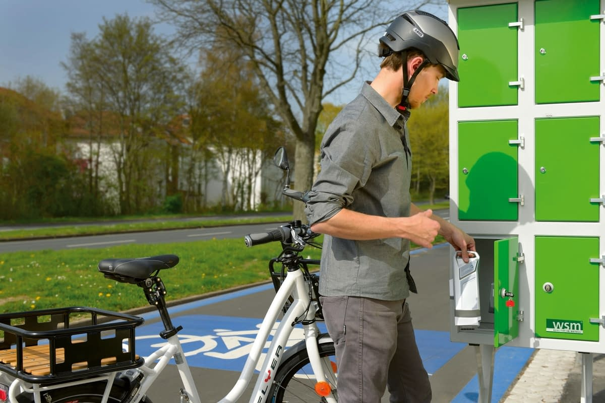 Electric cyclist on a cycle path in front of a locker