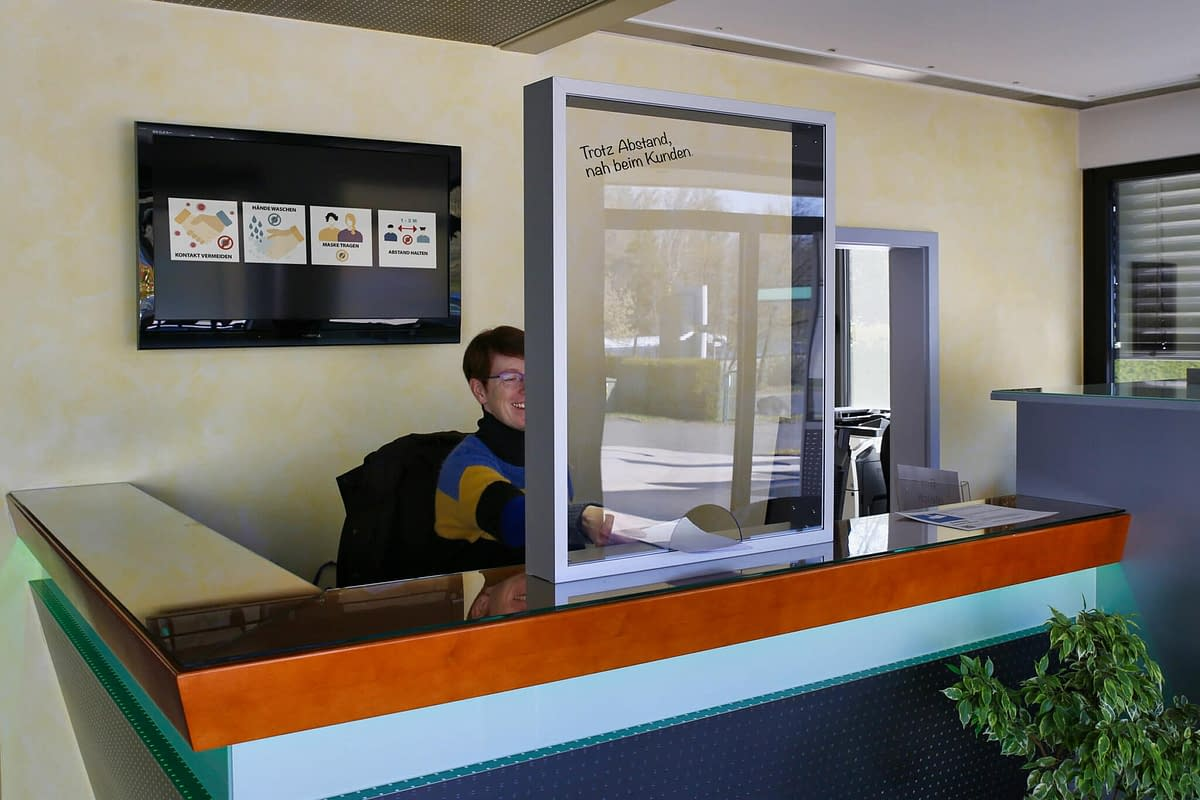 A spit guard with a pass-through stands on a reception counter